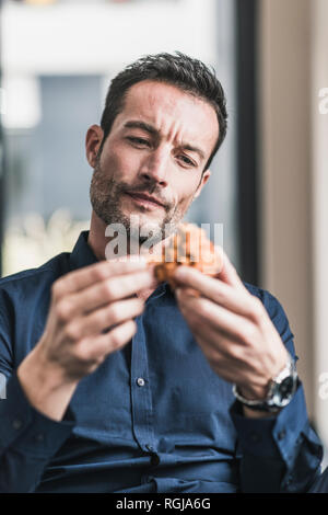 Mature man sitting in office assembling wooden cube puzzle - Stock Photo