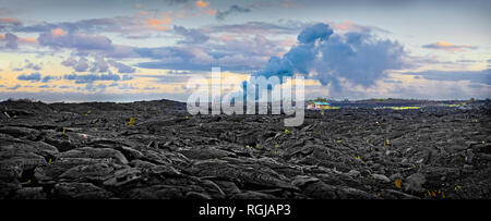 Volcanic rocky landscape with clouds and a house in the background. - Stock Photo