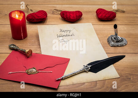 Vintage classic Valentine's Day love cad hand written vintage paper red envelope with wax seal cuddle hart candle silver quill stand on rustic oak - Stock Photo