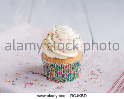Sprinkled vanilla cupcake with white chocolate butter cream frosting, on the kitchen white red towel on a white table. - Stock Photo