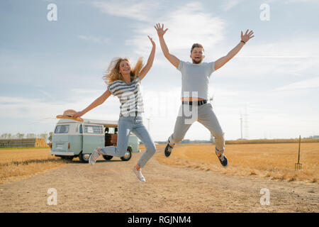 Exuberant couple jumping on dirt track at camper van in rural landscape - Stock Photo