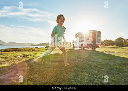 Chile, Talca, Rio Maule, boy running on meadowbeside camper at lake - Stock Photo