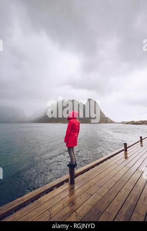 Norway, Lofoten, Hamnoy, man wearing red rain jacket standing on wooden stake looking at distance - Stock Photo