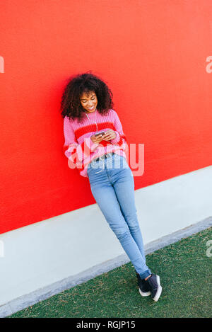 Smiling young woman with earphones leaning against red wall looking at cell phone