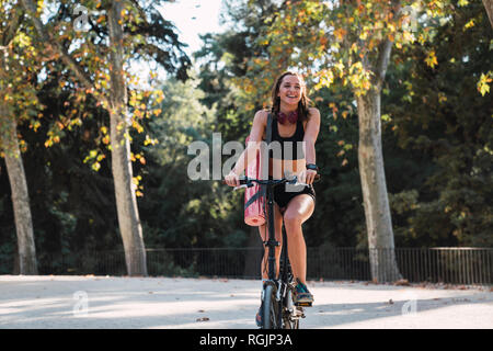 Fit young woman carrying yoga mat, riding bicycle - Stock Photo