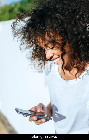 Smiling young woman looking at cell phone - Stock Photo