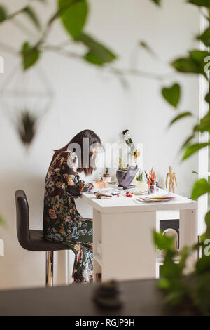 Illustrator painting at work desk in an atelier - Stock Photo