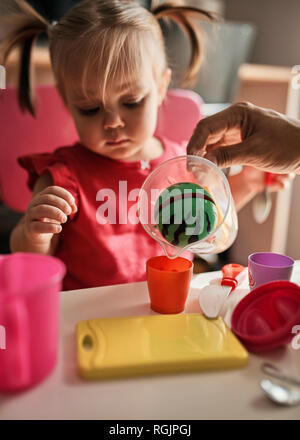 Little girl playing together with her father at home - Stock Photo