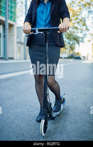 Close-up of businesswoman with scooter on the road - Stock Photo