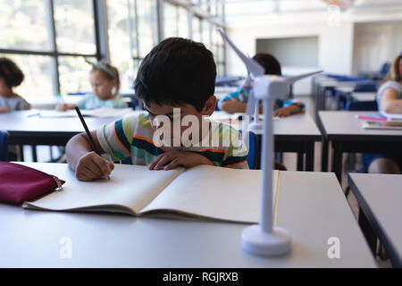 Front view of schoolboy writing on notebook at desk in classroom of elementary school - Stock Photo