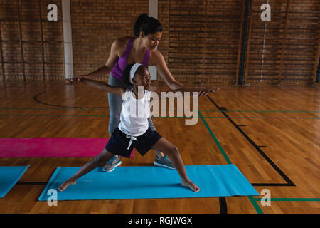 Female yoga teacher teaching yoga to school kids in school - Stock Photo