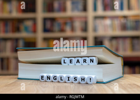 Dice in a book form the words 'learn English'. The book is lying on a wooden desk in front of a bookshelf. - Stock Photo