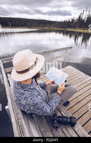 Sweden, Lapland, man with camera sitting on bench on a jetty looking at map - Stock Photo