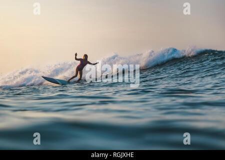Indonesia, Bali, Batubolong beach, Pregnant woman surfing - Stock Photo