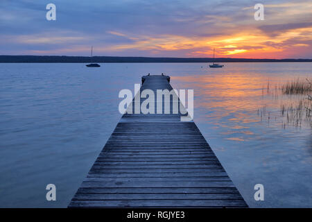 Wooden jetty at sunset at Lake Ammersee, Fuenfseenland, Bavaria, Germany. - Stock Photo