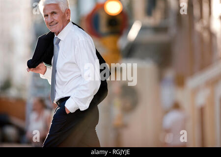 Mature businessman carrying his jacket over one shoulder smiles he poses for a portrait while crossing a city street. - Stock Photo