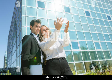 Smiling businesswoman and businessman taking a selfie outside office building - Stock Photo