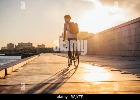 Young man with backpack riding bike on waterfront promenade at the riverside at sunset