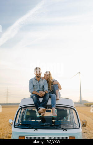 Portrait of happy young couple on roof of a camper van in rural landscape - Stock Photo