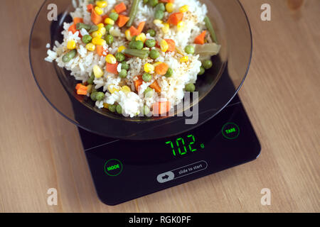 Translucent white plate with rice and vegetables is at home kitchen electronics scales to count calories in food on wooden table - Stock Photo