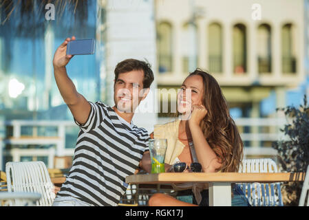 Happy young couple taking a selfie on the terrace of a bar - Stock Photo