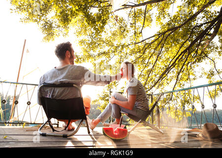 Young couple sitting on a jetty at a lake eating watermelon - Stock Photo