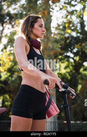 Fit young woman carrying yoga mat - Stock Photo