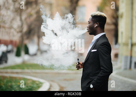 Portrait of a handsome young african man vaping an electronic cigarette on the street urban background - Stock Photo