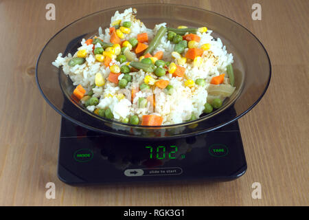 Translucent white plate with rice and vegetables is at home kitchen electronics scales to count calories in food on wooden table. Photo closeup - Stock Photo