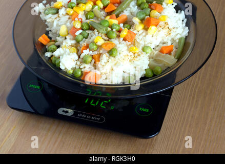 Translucent white plate with rice and vegetables is at home kitchen electronics scales to count calories in food on wooden table closeup - Stock Photo
