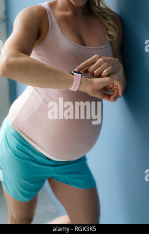 Mid-section of pregnant woman standing at blue wall looking at smartwatch
