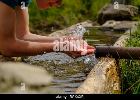 Germany, Upper Bavaria, Chiemgau, Young man refreshing at a fountain - Stock Photo