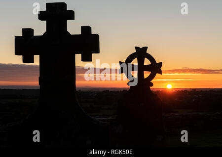 United Kingdom, England, Old Sodbury, Church of Saint John the Baptist, grave yard, crosses at sunset - Stock Photo