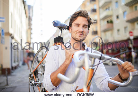 Portrait of content young man carrying his racing cycle on shoulder in the city - Stock Photo