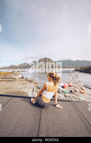 Norway, Lofoten, back view of woman looking at distance - Stock Photo