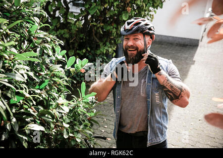 Portrait of laughing man putting on bicycle helmet - Stock Photo