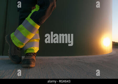 Legs of an engineer standing at a wind turbine tower - Stock Photo