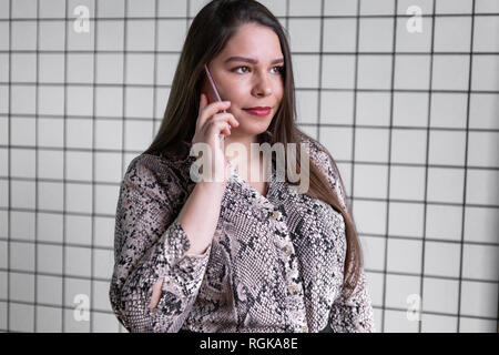 Close up young office woman talking to someone on her phone - Stock Photo