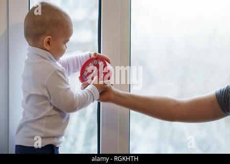 Mother and child are sitting on windowsill. Woman gives her son an alarm clock. Winter day outside window. Warmly family relationships. - Stock Photo