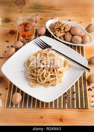 Fettuccine pasta with walnut cream on white plate on wooden table - Stock Photo