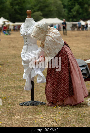 Duncan Mills, CA - July 14, 2018: Lady dressed in costume arrangng undergarments at a civil war re-enactement. The Civil War Days is one of the larges - Stock Photo