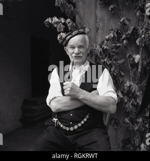 1950s, historical, portrait of an elderly German man in national costume sitting outside smoking a traditional Bavarian longpipe, Bavaria, Germany - Stock Photo