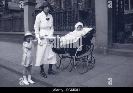 1920s, historical, on a pavement outside in a street, an elegant lady in dress of the day, possibly a nanny given her white dress, with a young girl and infant child sitting in a traditional coachbuilt baby carriage or pram, England, UK. With its large back wheels and suspension, this pram was comfortable for both the child riding in it and the mother or nanny pushing it. - Stock Photo