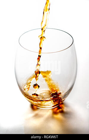 Pouring whiskey from bottle in to glass without ice cubes on white table. With copy space. - Stock Photo