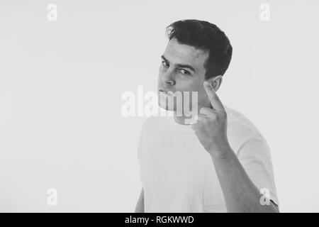 Close up portrait of an attractive young caucasian man with angry face looking furious and crazy showing teeth and fist isolated on white background.  - Stock Photo