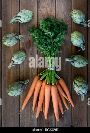 artichokes and carrots on wooden table - Stock Photo