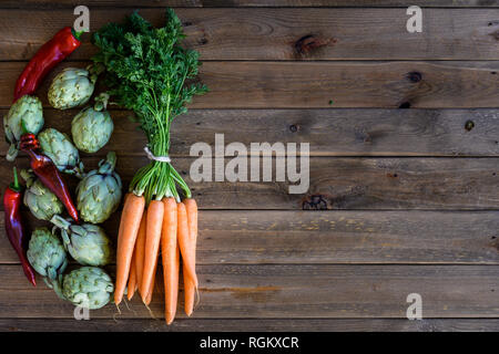 artichokes, peppers and carrots on wooden table - Stock Photo