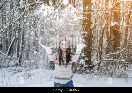 A woman in the snow-covered forest throws snow with her hands up on the background trees. Winter fun, relaxation, entertainment - Stock Photo