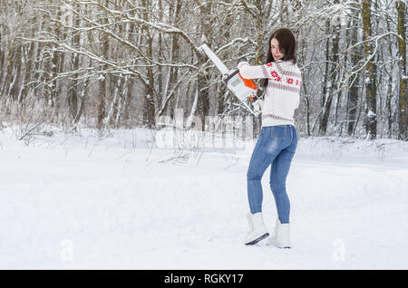 Cute cheerful girl goes through the snow in the woods with a chainsaw. Deforestation, logging firewood, equipment lumberjack - Stock Photo