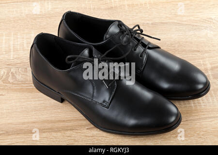 Close up picture of mens footwear Black leather elegant shoes on wooden background - Stock Photo